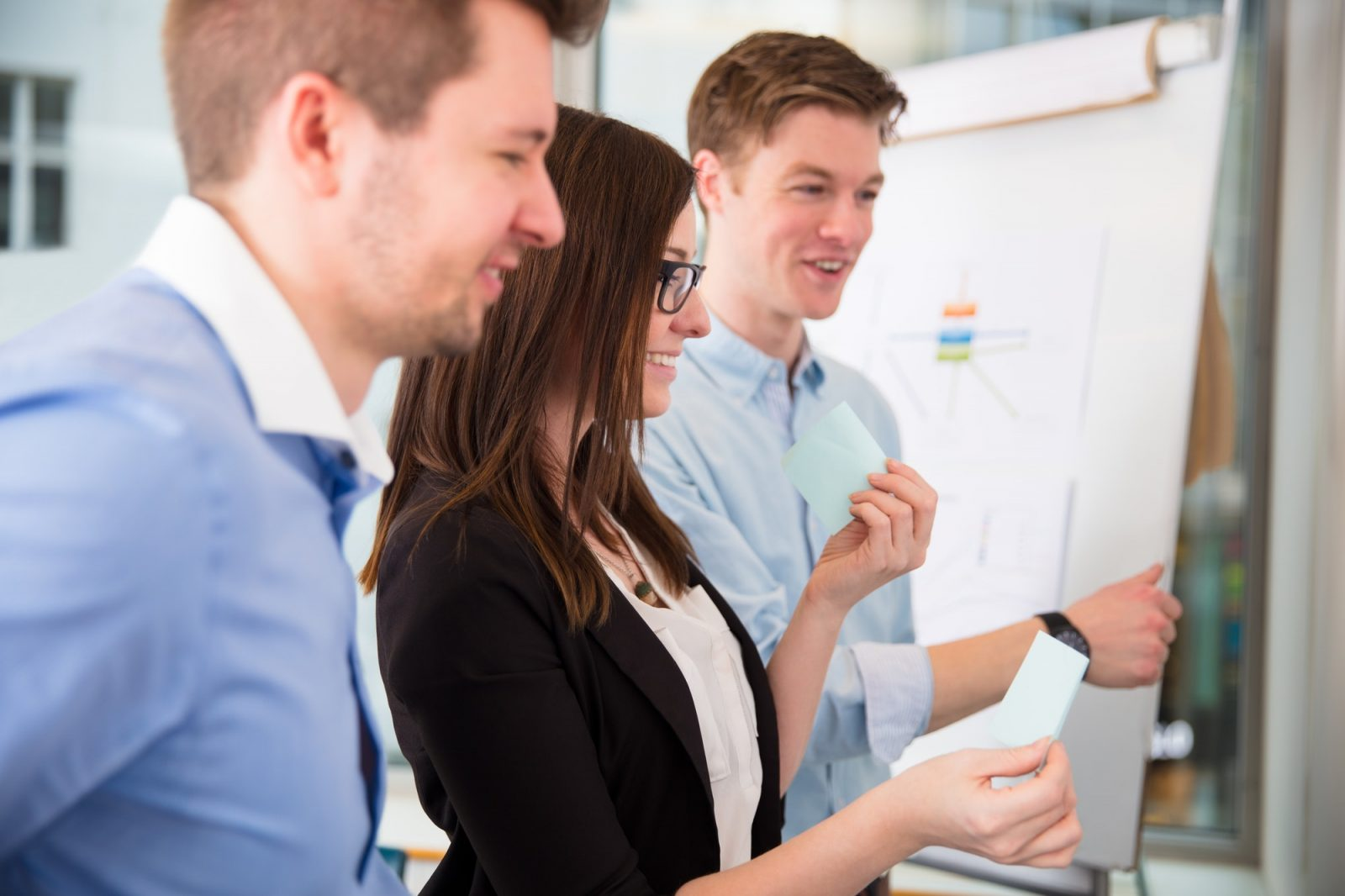 Smiling Businesswoman Holding Adhesive Note By Colleagues